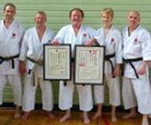 Reading Karate Sensei Malcolm (centre, holding certificates) is awarded 8th Dan